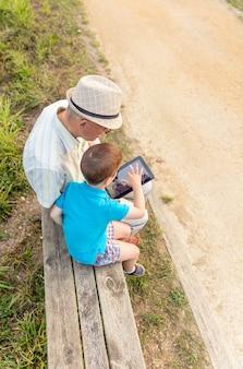 Kleinkind leert zijn grootvader om een elektronische tablet te gebruiken op een bankje in het park. generatie waarden concept.