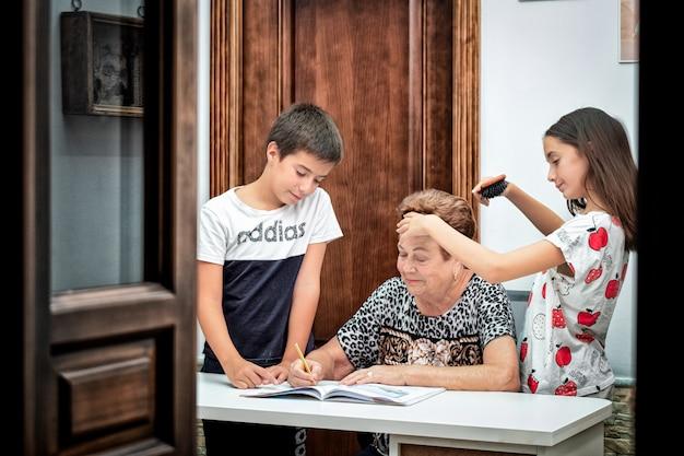 Kleinkinderen helpen oma met huiswerk en haar haren kammen