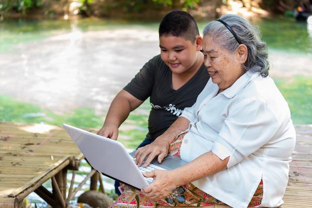 Kleinzoon die zijn bejaarde vrouwelijke gebruikslaptop onderwijst