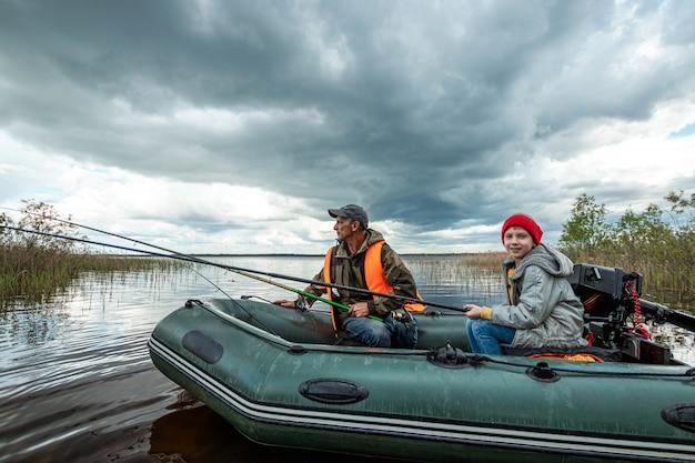 Kleinzoon en grootvader vissen samen vanaf een boot op het meer.