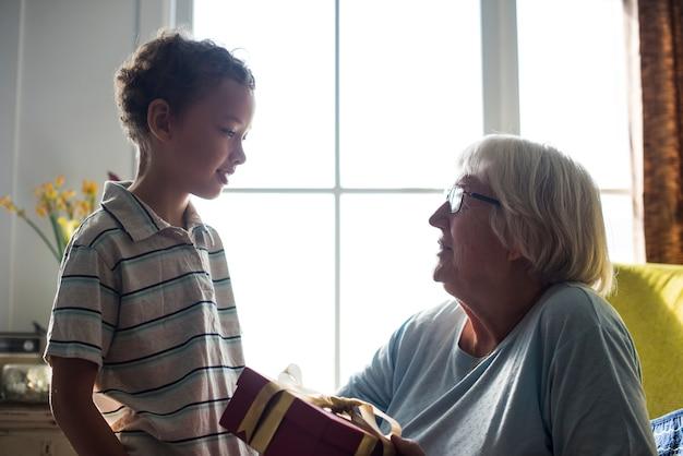 Kleinzoon geeft een cadeau aan zijn oma
