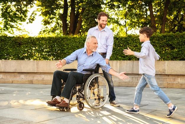 Kleinzoon kom naar gepensioneerde in rolstoel zitten.