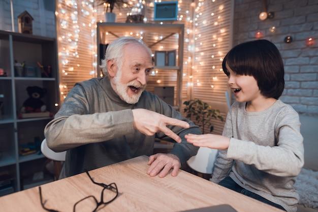 Kleinzoon met grootvader speel rock paper scissors