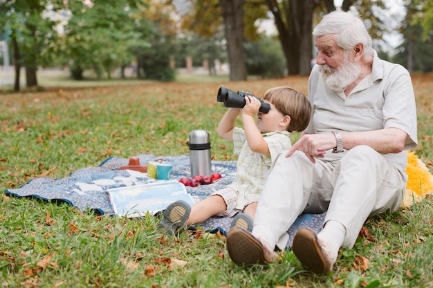 Kleinzoon met opa die door verrekijker kijkt