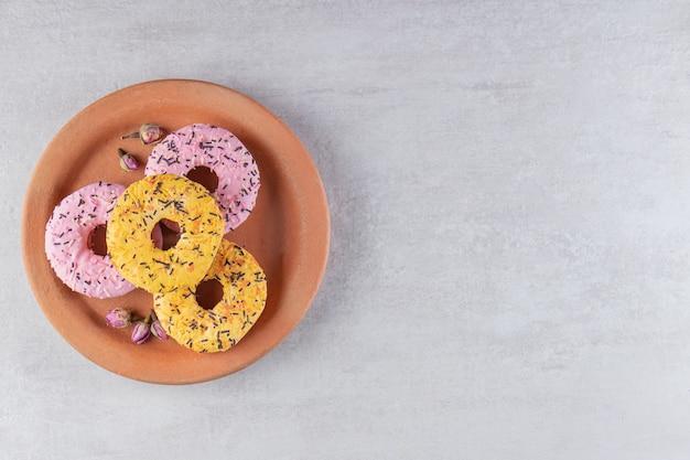 Kleiplaat van donuts versierd met hagelslag op stenen tafel.
