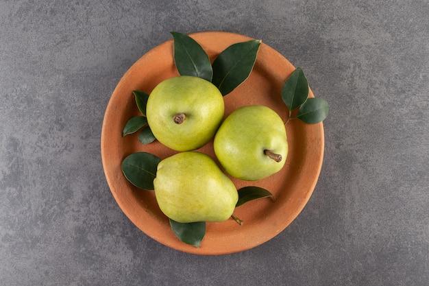 Kleiplaat van rijpe gezonde peren op steenoppervlakte