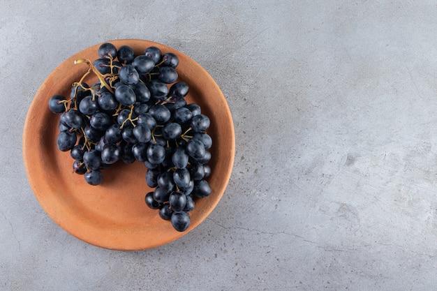 Kleiplaat van verse zwarte druiven op steenachtergrond.
