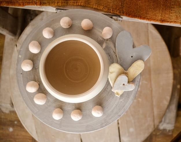 Kleipot bovenop een pottenbakkersschijf. abstract bovenaanzicht van een keramische pot