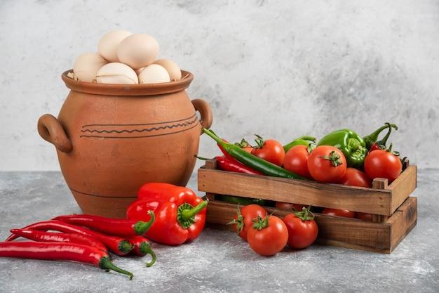 Kleipot vol rauwe kippeneieren en verse groenten op marmer.