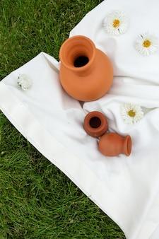 Kleipotten op een wit tafelkleed op het gras. bovenaanzicht.