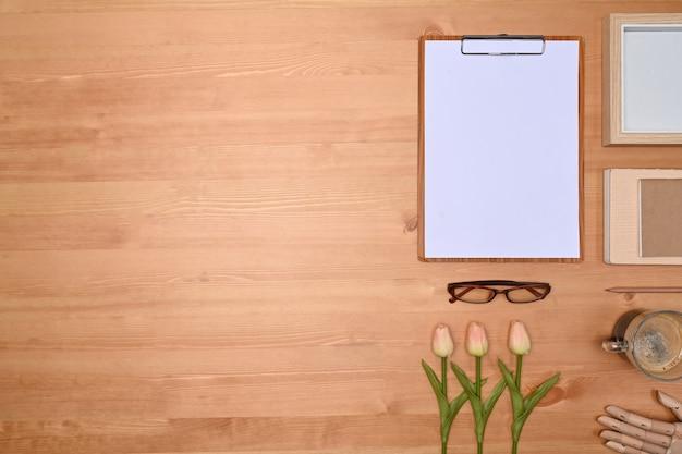 Klembord, afbeeldingsframe, bloemen en koffiekopje op houten achtergrond.
