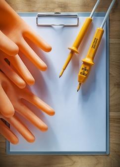 Klembord blanco papier elektrische tester isolerende handschoenen op een houten bord