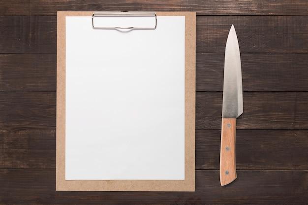 Klembord en mes op houten achtergrond wordt geplaatst die. kopieer ruimte voor uw tekst