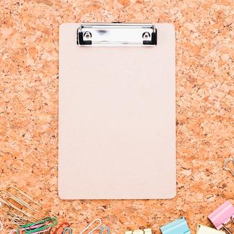 Klembord en veelkleurige paperclips geplaatst op kurk boord
