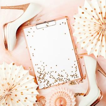 Klembord en vrouwelijke schoenen met gouden versieringen. plat lag, bovenaanzicht trendy vakantieconcept.