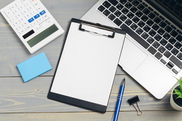 Klembord met blanco papier voor copyspace en benodigdheden op houten tafel