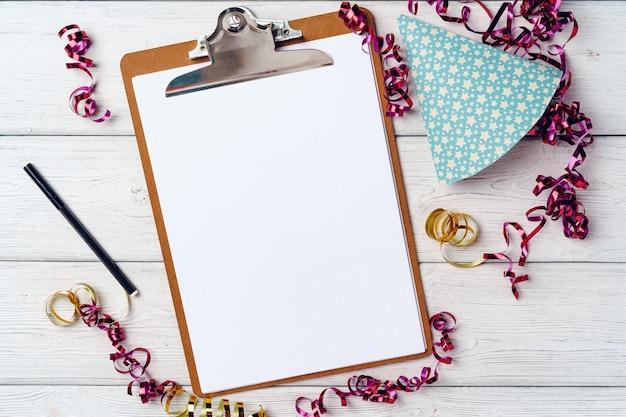 Klembord met blanco vel papier en partij streamers op witte houten tafel, bovenaanzicht