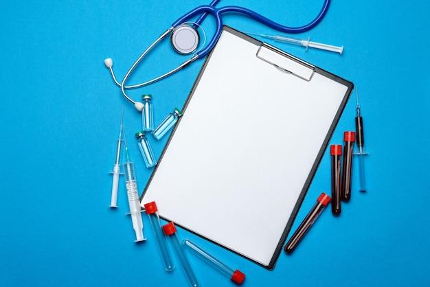 Klembord met blanco vel papier met medische hulpmiddelen op blauw