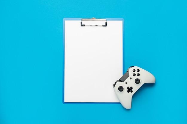 Klembord met een blanco vel en een gamepad op een blauwe achtergrond. banier. plat lag, bovenaanzicht.