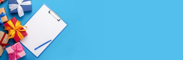 Klembord met een blanco vel en geschenken geïsoleerd op blauw