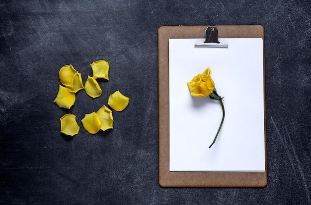 Klembord met en een kroonblad van gele roos op zwarte achtergrond. valentijnsdag
