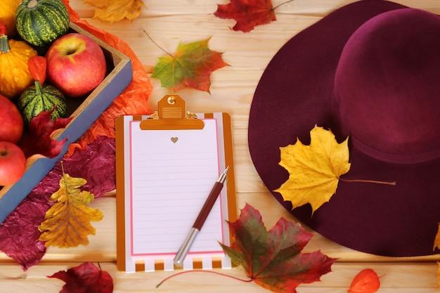 Klembord met esdoornbladeren, pompoenen en appels