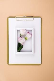 Klembord met eustomabloem en wit frame op beige oppervlak, platliggend. postkaartmodel