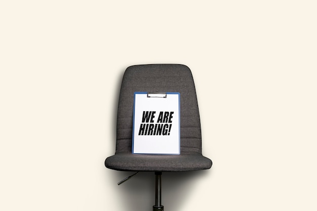 Klembord met het opschrift dat we inhuren ligt op een grijze bureaustoel op een witte achtergrond.