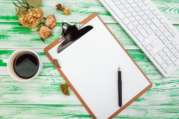 Klembord met kantoorbenodigdheden op groene houten tafel