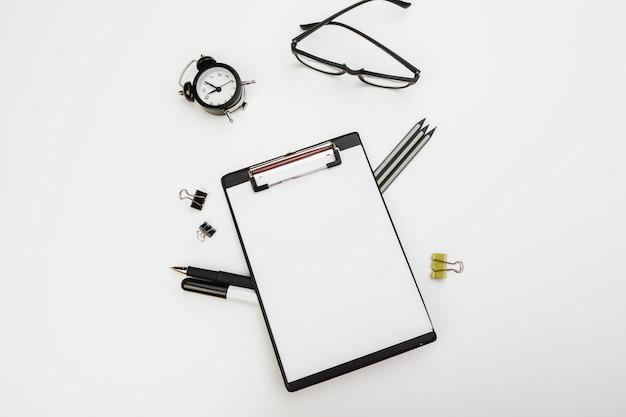 Klembord met kantoorbenodigdheden op witte tafel, bovenaanzicht
