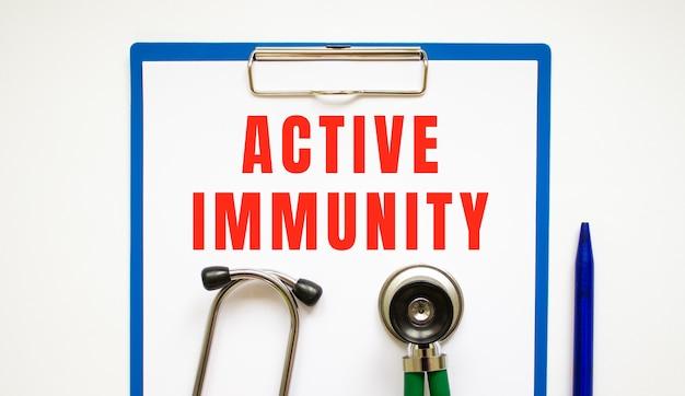 Klembord met pagina en tekst actieve immuniteit op een tafel met een stethoscoop en pen.
