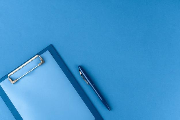 Klembord met pen op blauwe achtergrond, bovenaanzicht