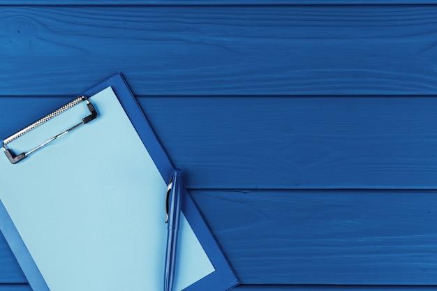Klembord met pen op blauwe tafel, bovenaanzicht