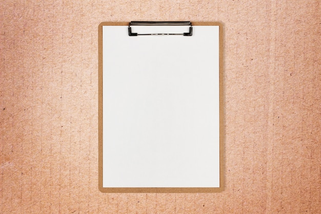 Klembord met wit blad en ruimte voor tekst op ambachtelijke papier achtergrond