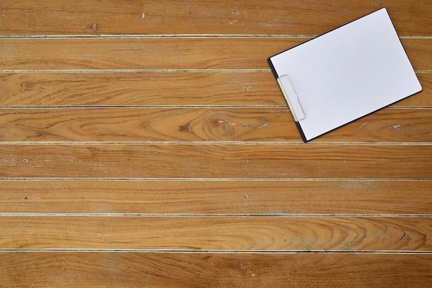 Klembord met wit blad op houten achtergrond