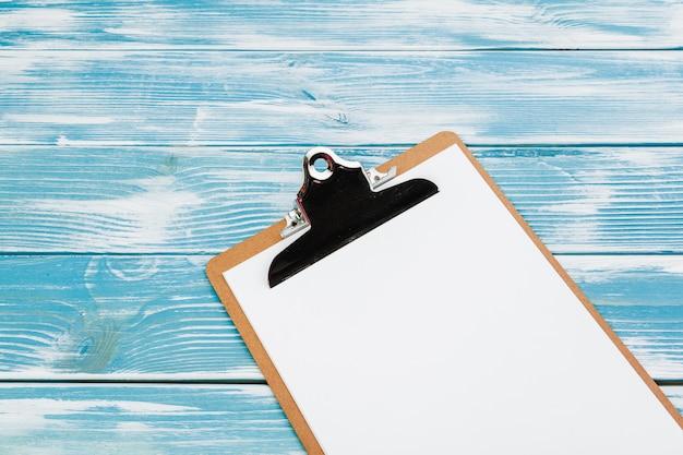 Klembord met witte blanco papier op blauwe houten tafel