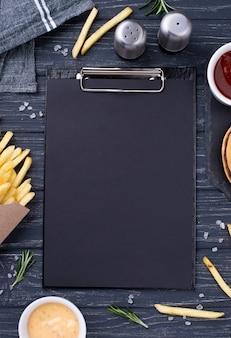 Klembord naast smakelijke hamburger met frietjes