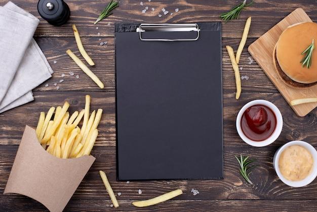 Klembord op tafel met hamburger en frietjes