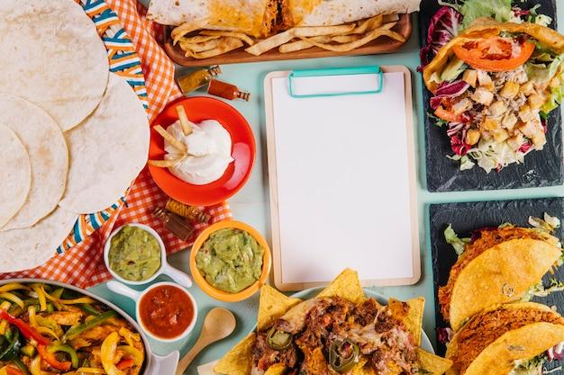 Klembord tussen smakelijke mexicaanse gerechten