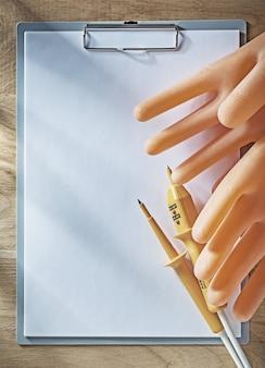 Klembordpapier elektrische tester diëlektrische handschoenen op een houten bord