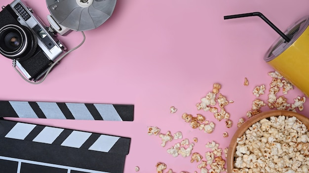 Klepelbord, retro camera en popcorn op roze achtergrond.
