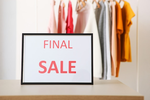 Kleren aan de rails en een verkoopbord met kortingen voor de laatste verkoop