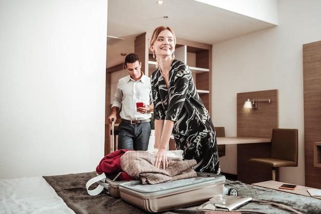 Kleren uit. blondharige vrouw voelt opgewonden haar kleren uit de bagage te halen die een reis met echtgenoot hebben