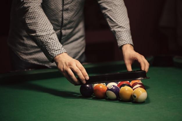 Kleur ballen van amerikaans biljart in driehoek op biljarttafel en biljart speler close-up