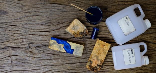 Kleur blauwe epoxyhars mengen in een glazen beker voor het gieten van wortelhout op oude houten ondergrond