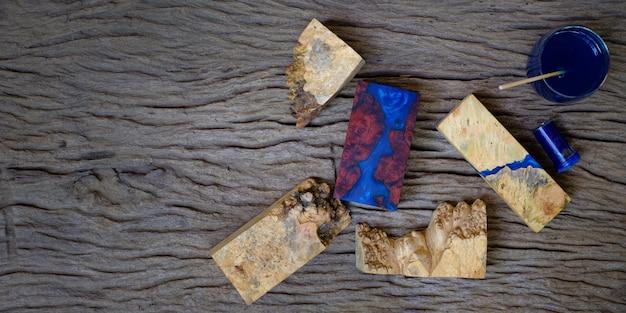 Kleur blauwe epoxyhars mengen in een glazen beker voor het gieten van wortelhout op oude houten tafelachtergrond