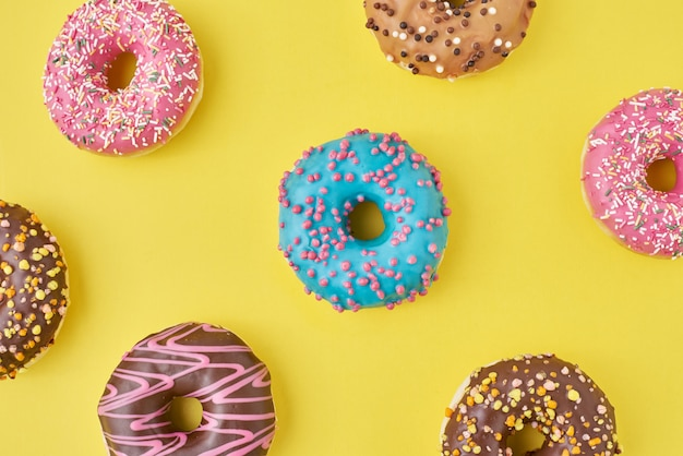 Kleur donut patroon op gele achtergrond, bovenaanzicht plat lag