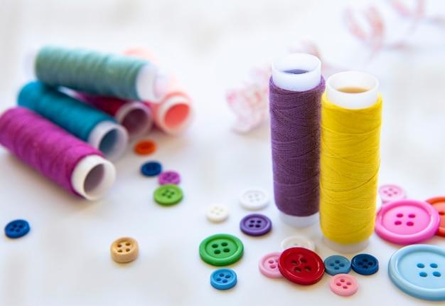 Kleur draden en naai-accessoires op wit oppervlak