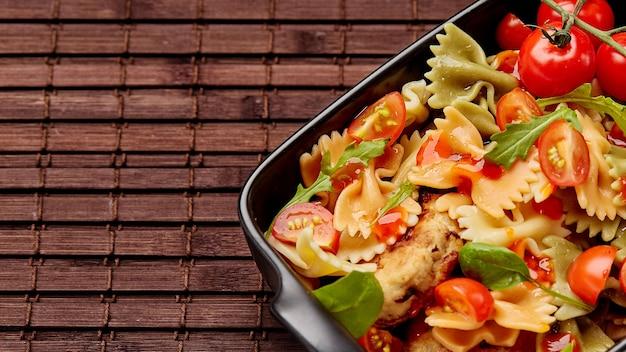Kleur farfalle kant-en-klare pasta met kipkoteletten met kruiden en tomaten.