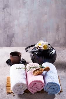 Kleur handdoeken met groene bladeren, lepel zout en detox thee op bamboe mat en stenen tafel